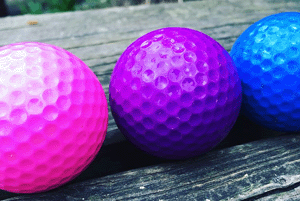 Golf balls, in pink, purple, and blue